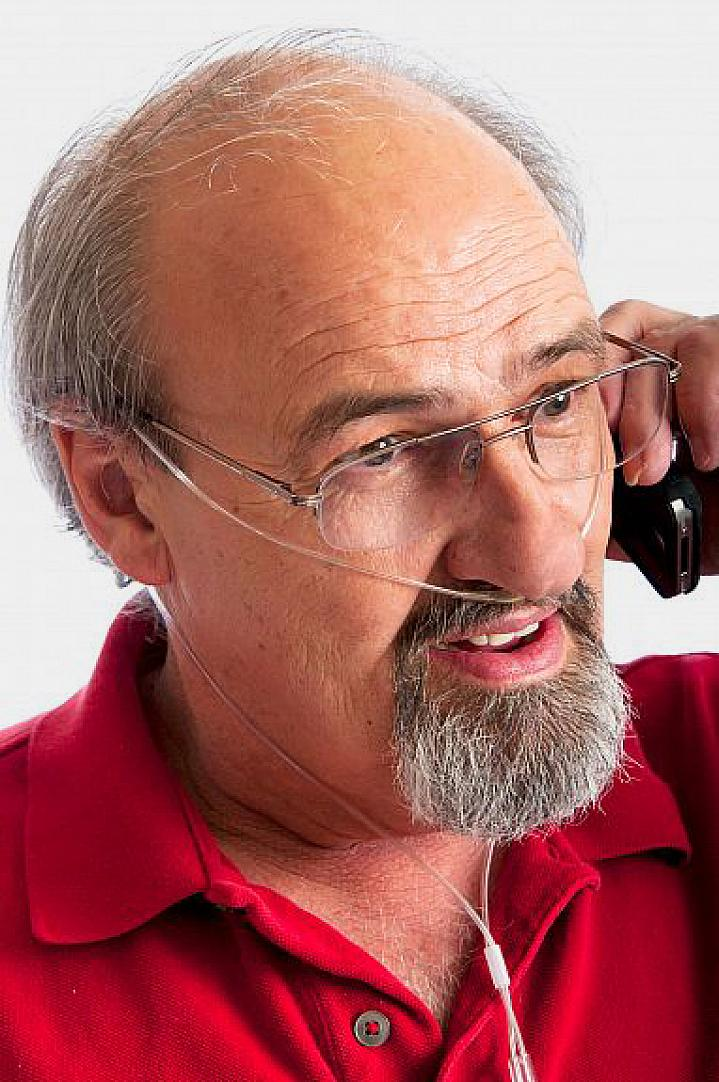 Man talking on phone while breathing in oxygen through a thin nasal tube.