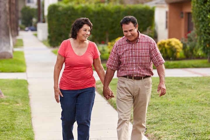 Senior Hispanic couple walking and holding hands on a sidewalk.