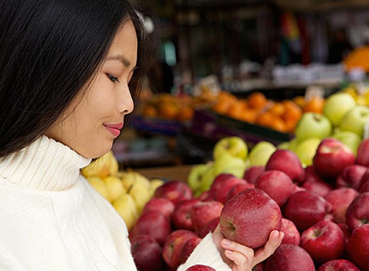 Young woman in grocery store looking at apples.