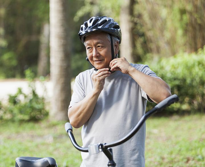 Older man buckling his bike helmet
