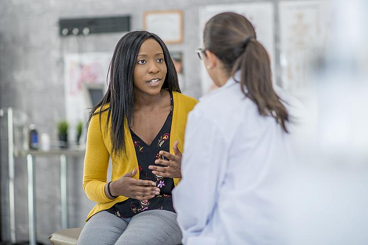 Woman describing her symptoms to a doctor