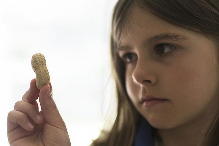 Girl looking skeptically at a peanut