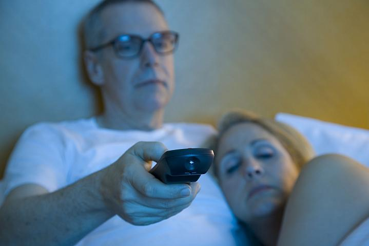 Sleepy couple watching television in bed