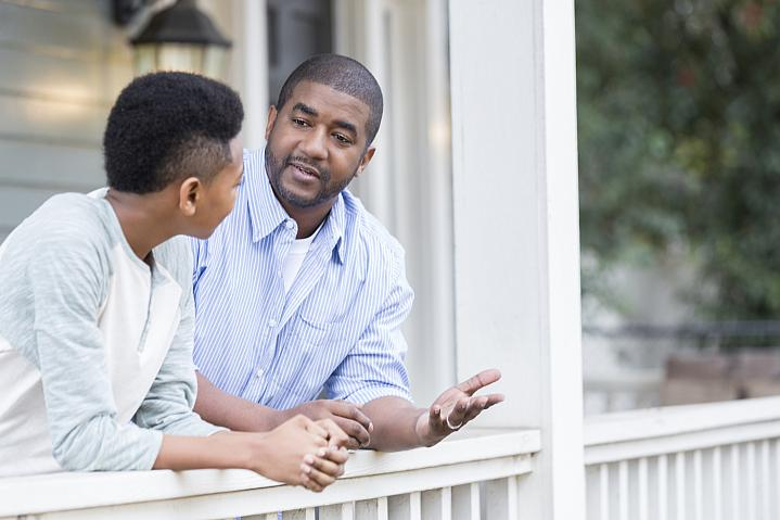 Father talking with his son on the porch