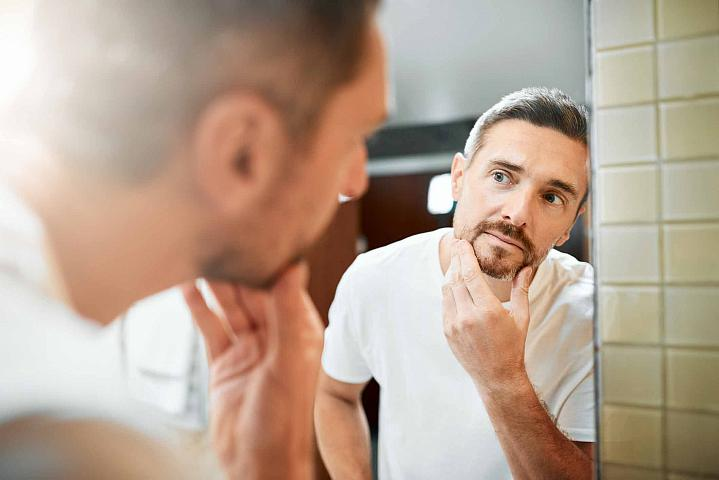 Man looking in the mirror at the gray hair in his beard