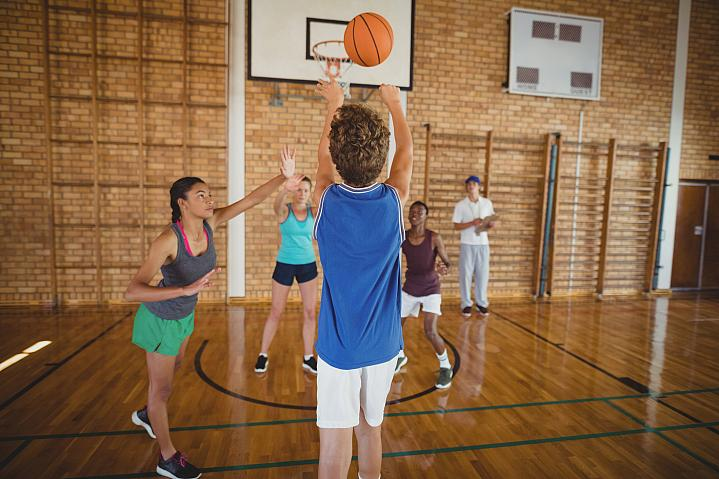 High school kids playing basketball in a gym