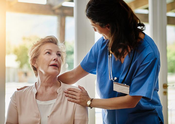 Health care provider smiling while talking to an older adult