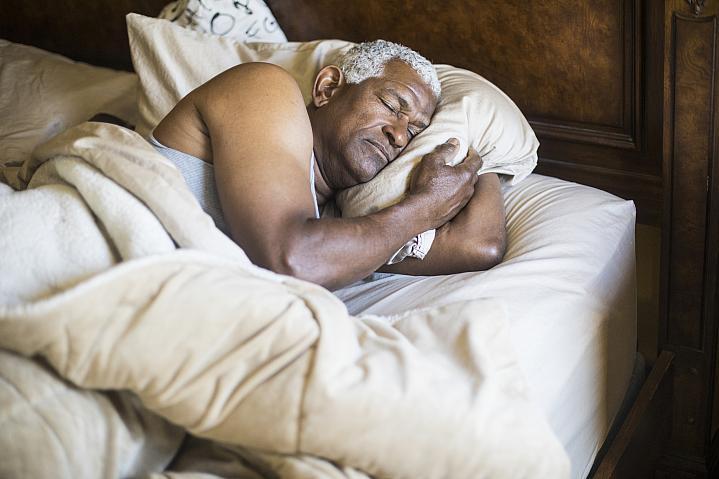 Older African American man asleep in bed