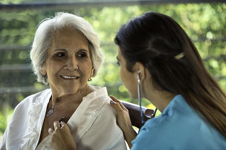 Physician listens to her senior patient's heart