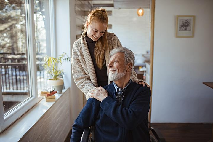 Young woman helping her older father